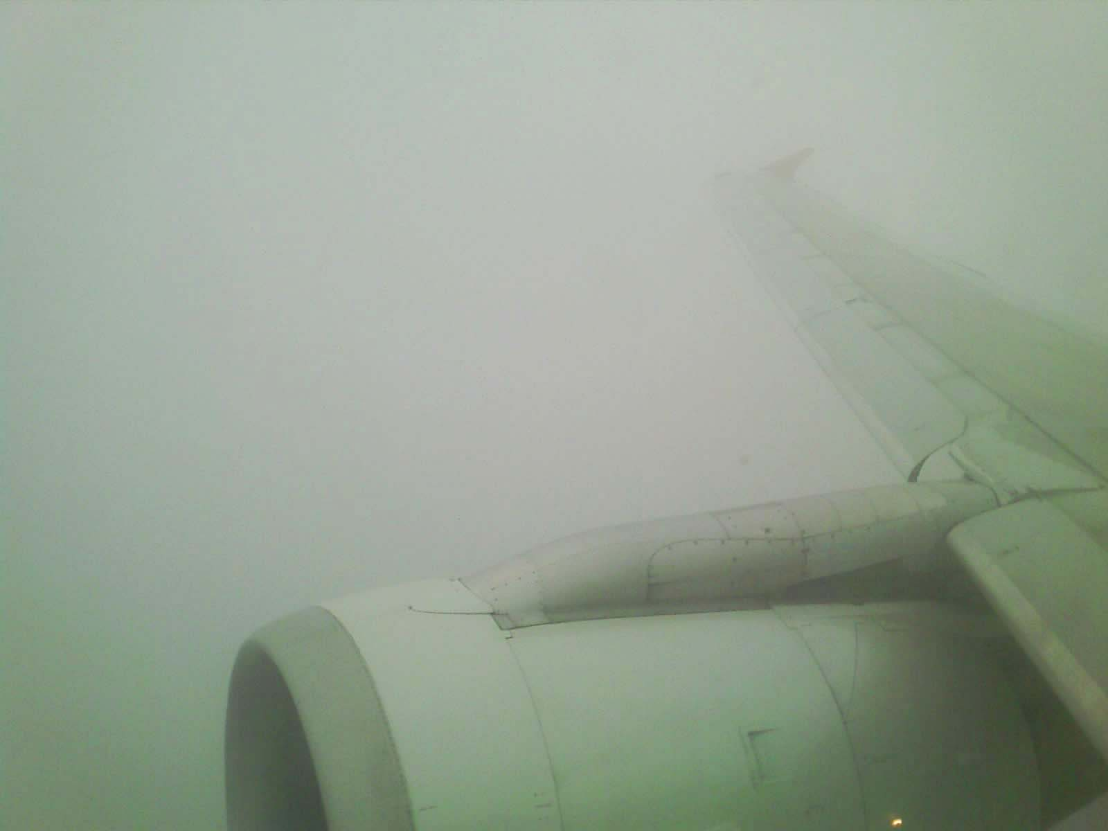 Looking out at the wing of an Northwest Airlines Airbus A320 while in the clouds