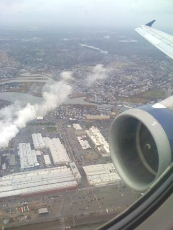A GE/CFM56 jet engine flying over the GE Lynn MA jet engine facility